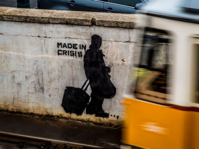 """Image of graffiti on a wall that reads """"Made in Crisis"""""""